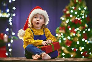 Fotos Neujahr Feiertage Kleine Mädchen Sitzend Mütze Geschenke Erstaunen kind