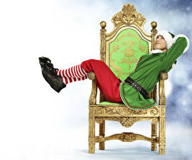 Photo New year Elves Armchair Sitting Uniform Legs Young man