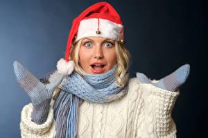 Bilder Neujahr Grauer Hintergrund Blond Mädchen Staunen Mütze Schal Fausthandschuhe junge Frauen