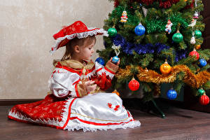 Images Christmas Holidays Christmas tree Little girls Dress Sitting Hat Balls child