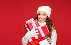 Photo Christmas Red background Brown haired Smile Gifts Winter hat Glove Girls