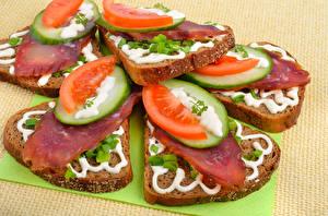 Bilder Butterbrot Brot Gurke Tomate Wurst Farbigen hintergrund