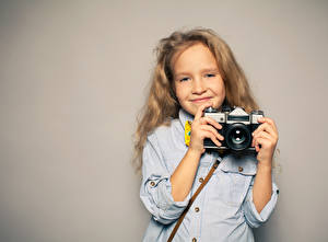Fotos Farbigen hintergrund Kleine Mädchen Lächeln Hand Fotoapparat Kinder