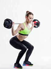 Bilder Fitness Weißer hintergrund Braunhaarige Hantelstange Körperliche Aktivität Kauert Mädchens