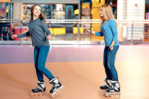 Image Two Roller skates Jeans Smile young woman Sport
