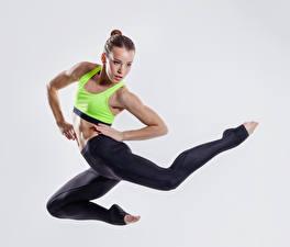 Wallpaper Fitness Gray background Brown haired Jump Hands Legs Girls Sport