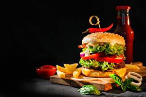 Fotos Hamburger Fritten Gemüse Schwarzer Hintergrund Schneidebrett Flaschen Ketchup das Essen