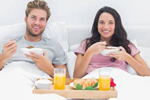 Bilder Mann Fruchtsaft 2 Brünette Frühstück Trinkglas Lächeln Starren Mädchens