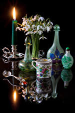 Pictures Still-life Snowdrops Bouquet Candles Black background Cup Bottle Reflection Flowers