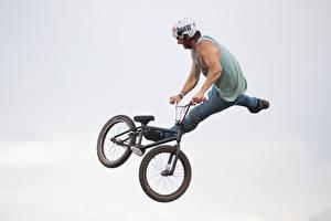 Bilder Mann Grauer Hintergrund Fahrrad Helm Sprung