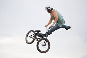 Pictures Man Gray background Bicycle Helmet Jump Sport