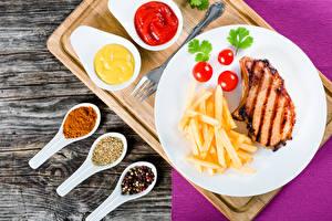 Bilder Die zweite Gerichten Fleischwaren Pommes frites Tomate Gewürze Bretter Teller Ketchup Lebensmittel