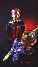 Pictures Still-life Irises Whiskey Black background Bottle Stemware