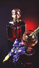 Pictures Still-life Iris Whisky Black background Bottles Stemware