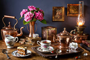 Images Still-life Kettle Bouquets Hydrangea Paraffin lamp Little cakes Tea Cup Book Sugar Food
