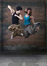 Fotos Mann Wände 2 Tanzen Sprung Glückliches Hand Mütze Mädchens