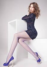 Hintergrundbilder Grauer Hintergrund Braune Haare Sitzend Starren Kleid Bein High Heels Mädchens