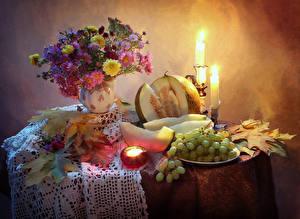 Bilder Stillleben Astern Kerzen Trauben Melone Tisch Vase Blattwerk Lebensmittel Blumen