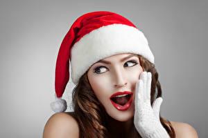 Bilder Neujahr Grauer Hintergrund Braune Haare Mütze Hand Blick Erstaunen Mädchens