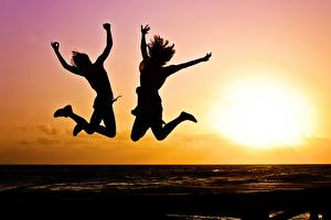Picture Sunrise and sunset Two Jump Silhouettes Sun Girls