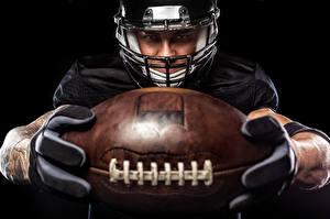 Bilder American Football Mann Schwarzer Hintergrund Uniform Ball Helm sportliches