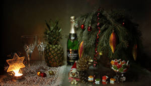 Pictures Christmas Still-life Sweets Champagne Pineapples Candles Branches Bottle Stemware Balls Snowflakes Conifer cone Food