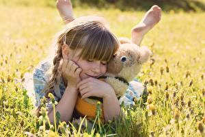 Fotos Teddybär Kleine Mädchen Gras Umarmung Kinder