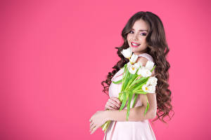 Pictures Tulips Colored background Brown haired Smile Glance Hair Beautiful Girls