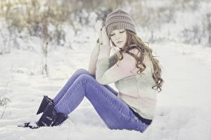 Bilder Winter Schnee Braune Haare Sitzend Mütze Bein Jeans Sweatshirt Mädchens