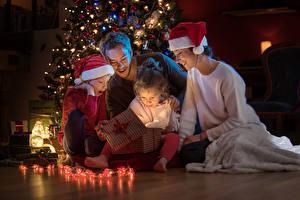 Fotos Neujahr Mutter Junge Kleine Mädchen Mütze Geschenke Lichterkette Kinder