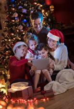 Hintergrundbilder Neujahr Tablet-PC Mutter Kleine Mädchen Junge Mütze Geschenke Kinder