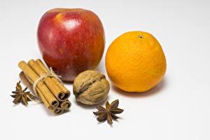Fotos Zimt Äpfel Apfelsine Schalenobst Walnuss Weißer hintergrund Lebensmittel