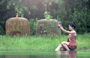 Pictures Water Asian Grass Brunette girl Sitting Girls