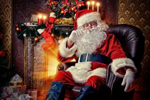 Bilder Kerzen Flamme Sessel Weihnachtsmann Sitzend Mütze Barthaar Brille Geschenke