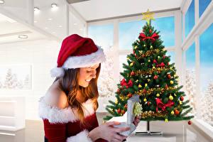 Hintergrundbilder Neujahr Braune Haare Geschenke Weihnachtsbaum Mütze Mädchens