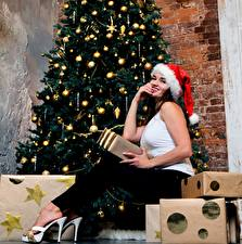Wallpapers Christmas Christmas tree Present Winter hat Brown haired Sitting High heels Balls Girls