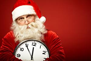 Photo New year Clock Clock face Red background Winter hat Glasses Bearded Staring