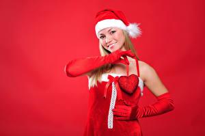 Bilder Neujahr Roter Hintergrund Blondine Mütze Lächeln Handschuh Herz junge Frauen