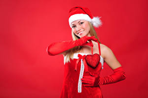 Pictures Christmas Red background Blonde girl Winter hat Smile Glove Heart female