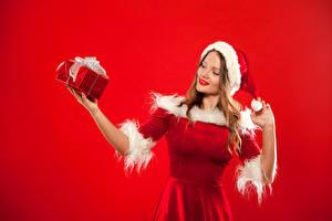 Fotos Neujahr Roter Hintergrund Blondine Mütze Geschenke Uniform Hand Mädchens