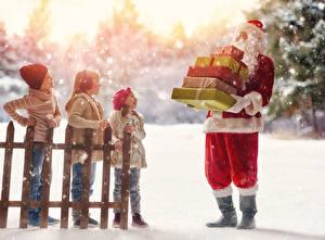 Bilder Neujahr Weihnachtsmann Junge Kleine Mädchen Zaun Mütze Geschenke Uniform Schnee kind