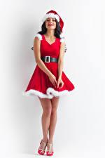 Bilder Neujahr Weißer hintergrund Brünette Uniform Lächeln Kleid Mütze Mädchens