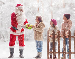 Hintergrundbilder Neujahr Winter Schnee Zaun Weihnachtsmann Junge Kleine Mädchen Geschenke Uniform Mütze kind