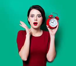 Images Clock Alarm clock Colored background Brunette girl Hands Surprise emotion Girls