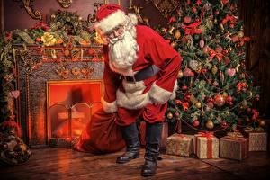 Pictures Fireplace New Year tree Present Santa Claus Bow Balls Winter hat Eyeglasses Beard Wearing boots