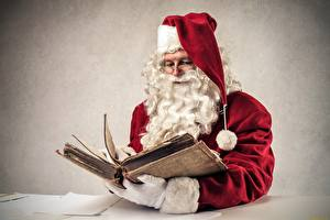Image Gray background Santa Claus Book Winter hat Eyeglasses Beard Sitting