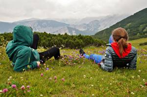 Pictures Mountain Austria Alps Grass Two Redhead girl Rest Jacket Hooded Nature