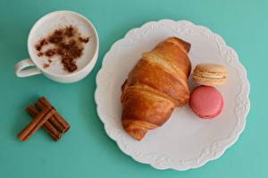 Fotos Cappuccino Zimt Kaffee Croissant Farbigen hintergrund Teller Tasse Macaron Lebensmittel