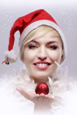 Pictures Christmas Blonde girl Winter hat Smile Staring Hands Balls Girls