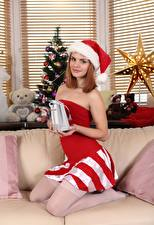 Wallpapers New year New Year tree Couch Gifts Winter hat Redhead girl Glance Smile female